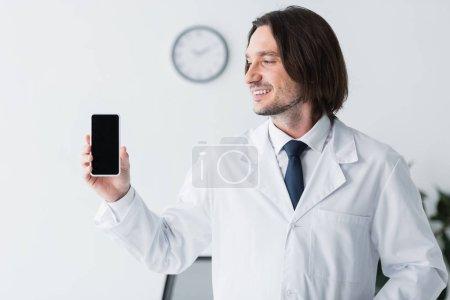 Photo pour Médecin heureux en manteau blanc tenant smartphone à la main et regardant l'affichage avec espace de copie - image libre de droit