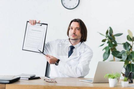 Photo pour Docteur dans le manteau blanc s'asseyant derrière la table en bois, regardant l'appareil-photo et pointant avec le stylo au document médical - image libre de droit