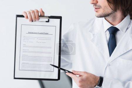 Photo pour Vue recadrée du docteur dans le manteau blanc pointant avec le stylo au document médical - image libre de droit