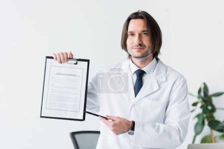 Photo pour Docteur de sourire dans le manteau blanc regardant l'appareil-photo et pointant avec le stylo au document médical - image libre de droit