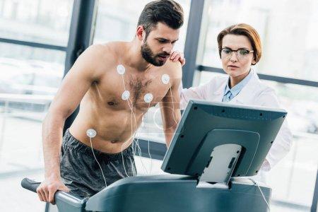 Photo pour Médecin effectuant un test d'endurance avec un sportif en salle de gym - image libre de droit