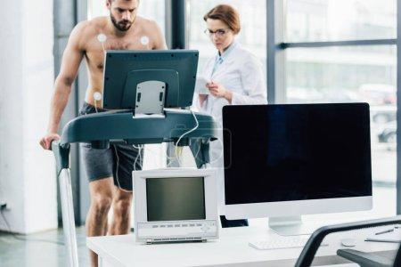 Photo pour Ordinateur avec écran vierge et médecin effectuant un test d'endurance avec sportif en salle de gym - image libre de droit