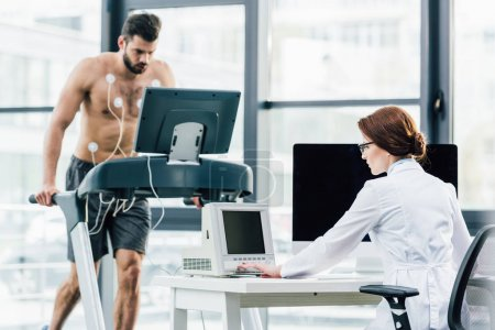 Photo for Doctor at desk conducting endurance test with sportsman in gym - Royalty Free Image