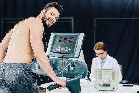 Photo pour Médecin effectuant un test d'endurance avec un sportif souriant dans la salle de gym - image libre de droit