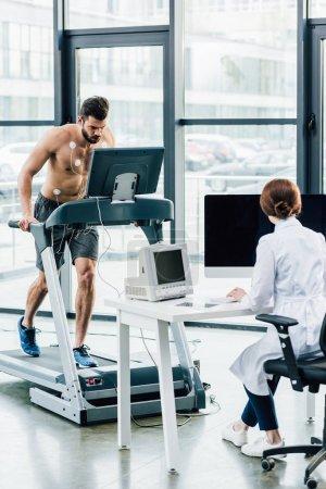 Photo pour Médecin assis au bureau de l'ordinateur et effectuant un test d'endurance avec un sportif dans la salle de gym - image libre de droit