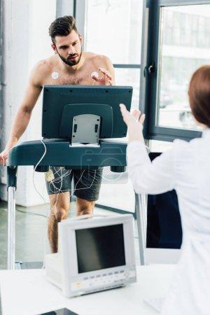 Photo pour Geste du médecin lors d'un test d'endurance avec un sportif en salle de gym - image libre de droit