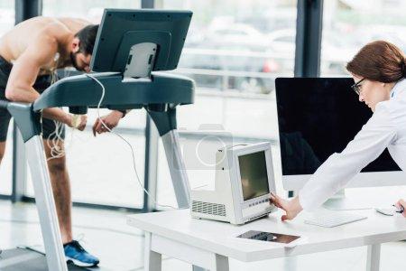 Photo pour Médecin regardant moniteur tout en effectuant un test d'endurance avec le sportif dans la salle de gym - image libre de droit