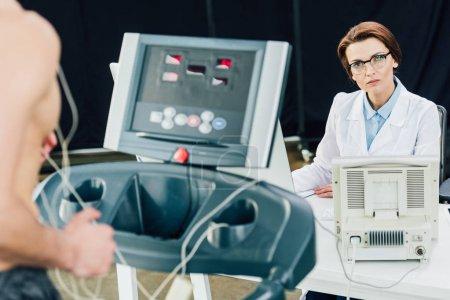 Photo pour Beau médecin effectuant un test d'endurance avec un sportif en salle de gym - image libre de droit
