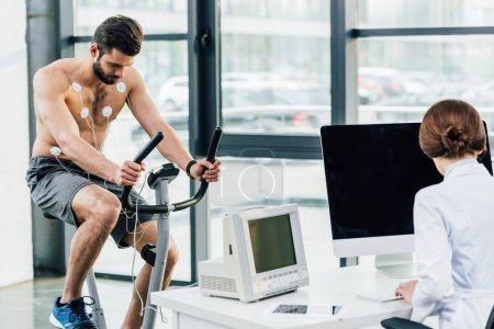 Photo pour Médecin effectuant un test d'endurance avec sportif avec électrodes dans la salle de gym - image libre de droit