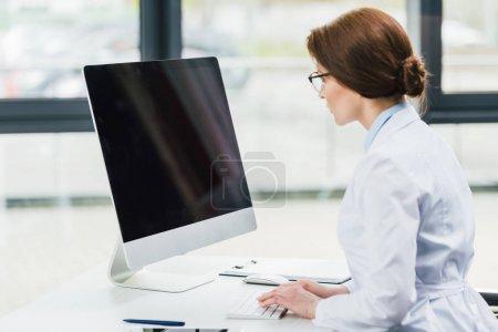 Photo pour Médecin en blouse blanche à l'aide de l'ordinateur avec écran blanc - image libre de droit
