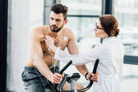 Photo pour Médecin effectuant un test d'endurance et mettant des électrodes sur sportif - image libre de droit