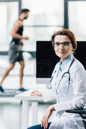 Photo pour Beau docteur s'asseyant au bureau d'ordinateur dans la gymnastique et regardant l'appareil-photo - image libre de droit