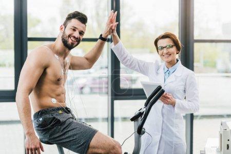 Photo pour Entraînement sportif sur machine elliptique et donner cinq médecin élevé pendant le test d'endurance - image libre de droit