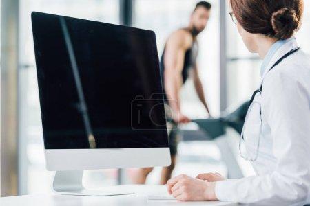 Photo pour Foyer sélectif du médecin assis près de l'ordinateur avec écran blanc dans la salle de gym - image libre de droit