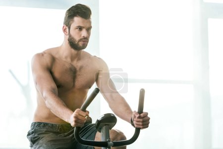Photo for Handsome sportsman training on elliptical machine at gym with copy space - Royalty Free Image