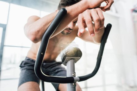 Photo for Selective focus of sportsman training on elliptical machine at gym - Royalty Free Image