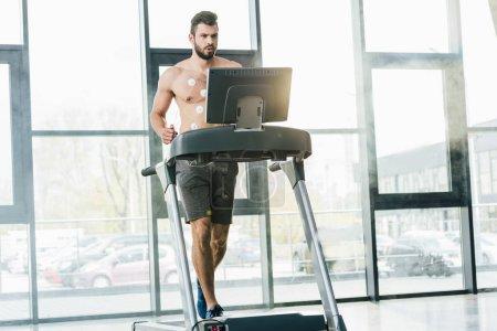 Photo pour Beau sportif avec des électrodes fonctionnant sur le tapis roulant pendant l'essai d'endurance dans la gymnastique avec la lumière du jour - image libre de droit