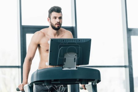 Photo for Shirtless handsome sportsman with electrodes running on treadmill during endurance test in gym - Royalty Free Image