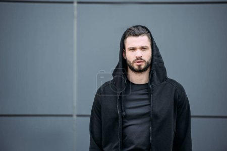 Photo for Handsome man in sportswear looking at camera near grey wall - Royalty Free Image