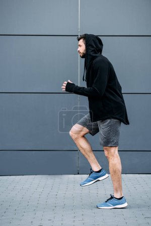 Photo for Side view of handsome sportsman in starting position ready to run - Royalty Free Image