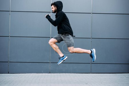 Photo for Side view of handsome sportsman jumping in sportswear - Royalty Free Image