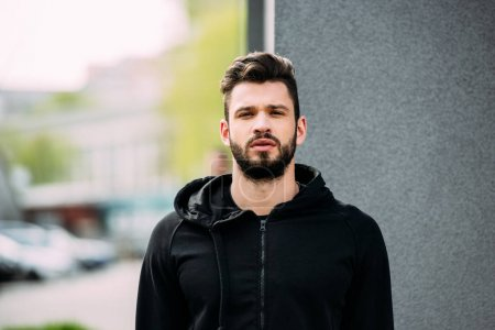 Photo for Handsome bearded man in sportswear looking at camera - Royalty Free Image