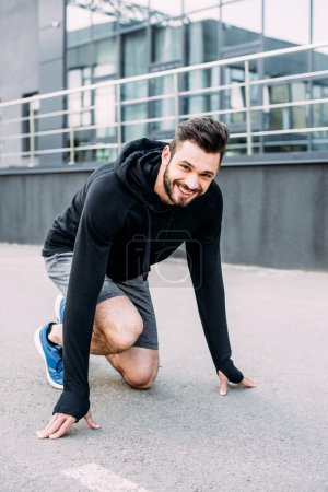 Photo for Smiling handsome sportsman in starting position ready to run - Royalty Free Image