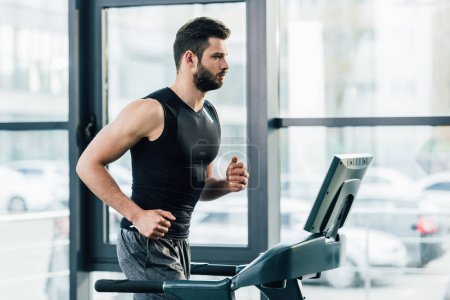 Photo for Handsome sportsman training on treadmill at sports center - Royalty Free Image