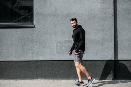 Foto de Hombre guapo en ropa deportiva posando cerca de la pared gris con el espacio de copia - Imagen libre de derechos