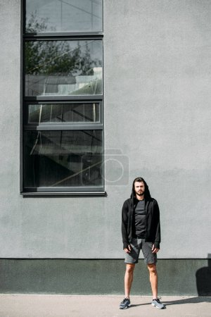 handsome man in sportswear posing near grey wall