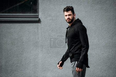Photo pour Bel homme en vêtements de sport regardant la caméra près du mur gris - image libre de droit