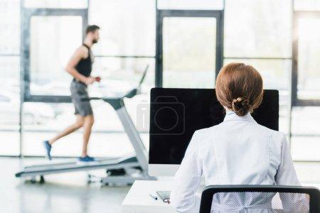 Photo pour Médecin utilisant l'ordinateur tandis que le sportif courant sur le tapis roulant pendant l'essai d'endurance dans la gymnastique - image libre de droit