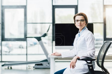 Photo for Doctor in white coat sitting at computer desk at gym and looking at camera - Royalty Free Image