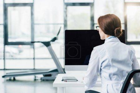 vue arrière du médecin en manteau blanc assis au bureau de l'ordinateur à la salle de gym