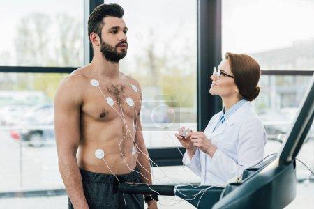 Photo pour Médecin effectuant un test d'endurance près du sportif avec des électrodes dans le centre sportif - image libre de droit