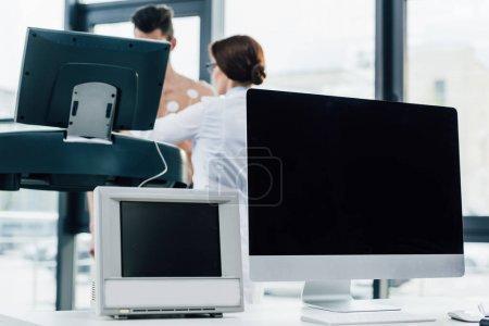 Photo pour Ordinateur et moniteur avec écran blanc et sportif en cours d'exécution sur tapis roulant près du médecin pendant le test d'endurance - image libre de droit