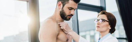 Photo pour Prise de vue panoramique du médecin effectuant un test d'endurance près du sportif avec des électrodes dans le centre sportif - image libre de droit