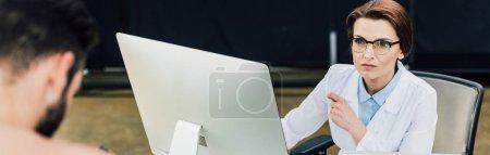 Photo pour Prise de vue panoramique du beau médecin assis au bureau de l'ordinateur près du patient - image libre de droit