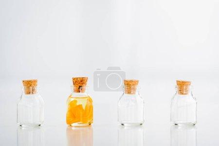 Photo pour Pot en verre bouchonné avec l'huile essentielle avec des tranches d'orange près des bocaux vides sur le fond blanc - image libre de droit