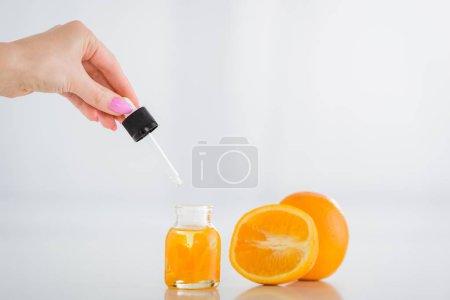 Photo pour Vue recadrée de la position de femme a chuté près de la bouteille avec l'huile essentielle orange et les oranges fraîches sur le fond blanc - image libre de droit