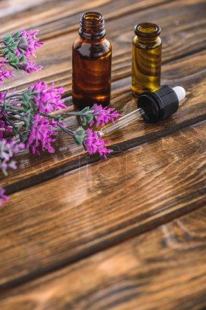 Photo pour Fleur de bruyère, bouteilles avec huile essentielle et compte-gouttes sur la surface en bois - image libre de droit