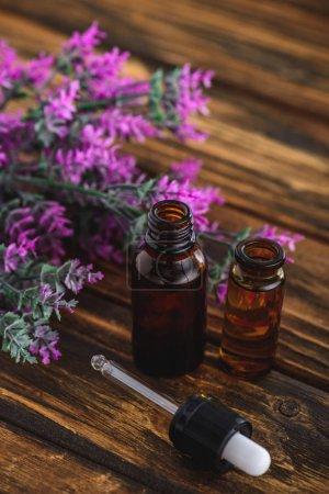 Photo pour Usine de bruyère, bouteilles avec huiles essentielles et goutte-à-goutte sur la surface en bois - image libre de droit