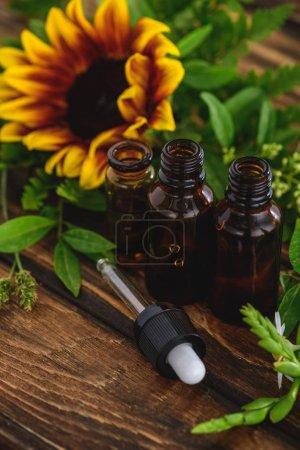 Photo pour Bouteilles avec huiles essentielles, compte-gouttes et tournesol sur surface en bois - image libre de droit