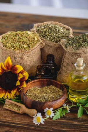 Photo for Wooden bowl and sackcloth bags with dried herbs, bottles with essential oils, sunflower and chamomile flowers on wooden surface - Royalty Free Image