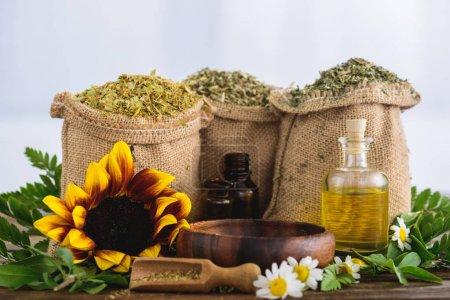 Photo pour Sacs à sac avec herbes séchées, bouteilles avec huiles essentielles, fleurs de tournesol et de camomille, bol en bois et spatule sur surface en bois - image libre de droit