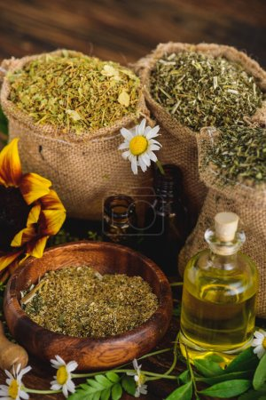 Photo pour Sacs à sac avec herbes séchées, bouteilles avec huiles essentielles et fleurs de camomille sur la surface en bois - image libre de droit