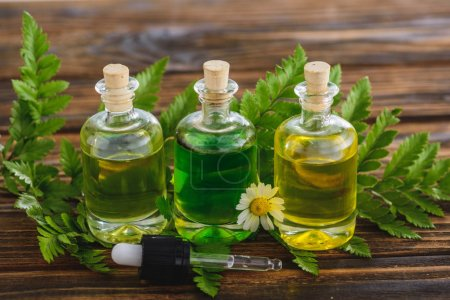 Photo pour Bouteilles bouchonnées avec huiles essentielles, goutte-à-goutte, feuilles de fougère et fleur de camomille sur la surface en bois - image libre de droit