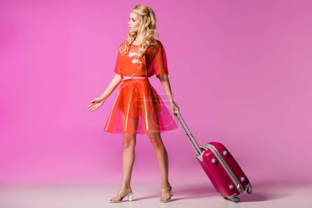Photo pour Beautiful girl with suitcase on pink, doll concept - image libre de droit