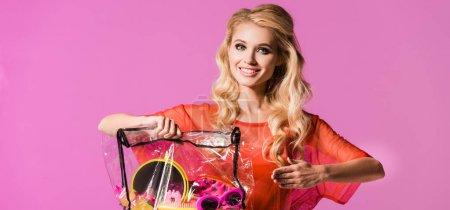 Foto de Foto panorámica de hermosa chica posando con bolsa cosmética transparente aislada en rosa, concepto de muñeca - Imagen libre de derechos