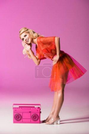 Photo pour Belle fille de sourire posant avec boombox sur le rose, concept de poupée - image libre de droit